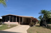 Palm trees surrounding house, oversized driveway, plenty of room for 2 cars & an outdoor covered seating area!